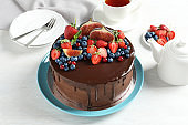 Fresh delicious homemade chocolate cake with berries on light table