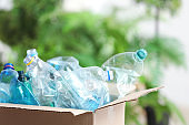 Cardboard box with used plastic bottles on blurred background. Recycling problem