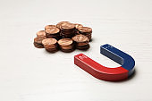 Magnet attracting coins on wooden background. Business concept