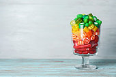 Glass of delicious chewing candies on wooden table against light background. Space for text