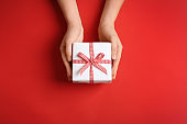 Woman holding gift box on color background, top view