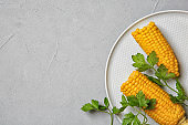 Plate with ripe corn cobs and parsley on grey background, top view. Space for text