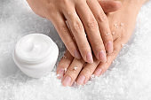 Woman holding hands near jar of cream on decorative snow. Winter skin care cosmetic