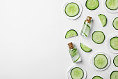 Flat lay composition with cucumber, bottles and cotton pads on white background