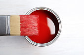 Paint can and brush on wooden background, top view