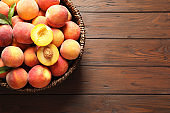 Wicker basket with fresh sweet peaches on wooden table, top view