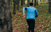 Rear view image of runner man running outdoor in the forest background. Fitness male exercising in the park, wearing blue and black sportswear. People and sport concept