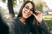 Beautiful young woman relaxing outdoor and taking self portrait on her smart phone. Female wears knitted sweater, transparent eyeglasses making selfie on mobile phone on the city street.