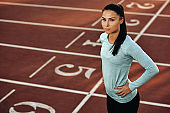 Horizontal outdoor image of young woman athlete posing on racetrack at stadium. Portrait of beautiful professional sportswoman during training session. People, sport and healthy lifestyle