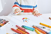 Horizontal cropped image of little girl playing with colors. Cute child painting with fingers on paper at the desk, at kindergarten. People, childhood, education
