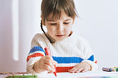 Creative little girl painting with colorful pencils, sitting at white desk at home. Joyful child drawing with pencils. People, childhood and education concept