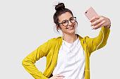 Pretty young European woman in casual clothes standing and taking a selfie isolated over white studio background. Pretty Caucasian brunette female wearing transparent spectacles making self portrait