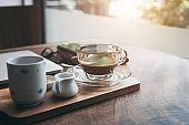 Coffee cup and tea put on wooden table with nature background