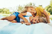 Happy children playing on the blanket outdoors. Cheerful little boy and cute little girl smiling and relaxing in the park. Kids having fun on sunlight. Sister and brother spending time together.