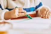 Cropped image of cute little girl paints with green oil pencil sitting at white desk at home. Image of pretty preschool kid draws on paper in the kindergarten. People, childhood and education concept