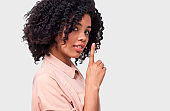 Confidential African American young woman dressed in pink shirt holding index finger on lips, asking to keep silence over white wall. Beautiful dark skinned female looks to the camera asks to be quiet