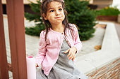 Horizontal image of cute little girl drinking water from her pink eco glass bottle sitting outdoor. Happy child pupil relaxing outside after preschool lessons. People, education concept