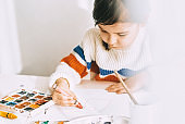 Indoor image of artistic little girl painting with oil pencils, sitting at white desk at home. Pretty smiling preschool kid drawing with pencils. People, childhood and education concept