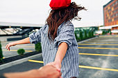 Rear view image of brunette young woman wearing blue shirt and red beret hat, holding a hand to follow her on the city street. Romantic female walking outdoors, follow me. People and lifestyle concept