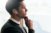 Pensive young handsome man have a call with a colleague and looking through the window in office, talking from wireless earphones. Caucasian businessman using wireless headphones during conversation.