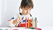 Cute child playing with colorful pencils at home. Happy kid drawing on paper in the kindergarten. People, childhood and education concept