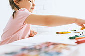 Little artist girl drawing with colorful pencils, wearing pink t-shirt. Cute preschooler child painting and learning at kindergarten. People, childhood, education