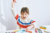 Happy little girl smiling and playing with colorful pencils. Joyful child drawing with colorful pencils on paper at the desk, feeling happy, sitting at home. People, childhood, education