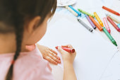 Rear view image of cute little girl drawing with colorful pencils, wearing pink t-shirt. Pretty preschooler child painting and learning at kindergarten. People, childhood, education