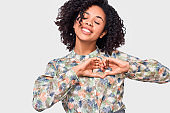 Smiling young African American woman making heart shape with fingers. Pretty Afro female dressed  floral pattern shirt, showing heart gesture with both hands, love sign, posing on white background