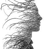 Double exposure of a young handsome man's profile portrait blended with many branches dissolving into his face, black and white