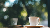 Coffee cup on the wooden table and green bokeh background.