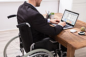 Businessman Sitting On Wheelchair Using Laptop