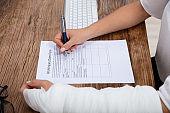 Injured Woman Filling Work Injury Claim Form