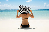 Woman In Bikini Looking At Ocean Wearing Sun Hat