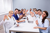 Doctors Waving Their Hands In Conference Room