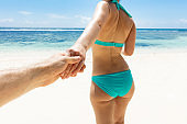 Woman In Bikini Holding Hand Of Her Boyfriend On Beach