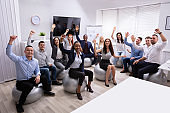 Group Of Happy Businesspeople Waving Hands