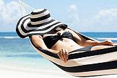 Woman Sleeping In Hammock At Beach