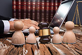 Separation Of Wooden Pawn Figures With Gavel