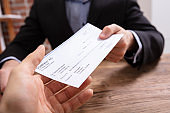 Man's Hands Giving Cheque To Other Person
