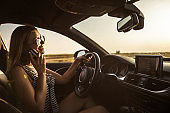 Happy young woman talking on the phone while driving a car