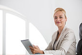 Smiling businesswoman looking at camera while using digital tablet at work