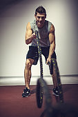 Athletic man using battle ropes at the gym