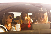 Three young females driving in the car in warm summer sunshine