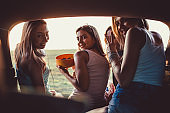 Four cheerful girlfriends enjoying snacks and relaxing while taking a break from their road trip