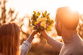 Couple holding a bouquet of flowers against sky