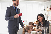 Mid adult parents having breakfast with their children before going to work