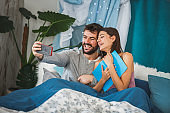 Smiling young couple taking a selfie while relaxing in bed