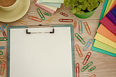 Clipboard with blank paper, messy multi colored paper clips and files