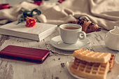 Coffee, waffles, smart phone and book on the table